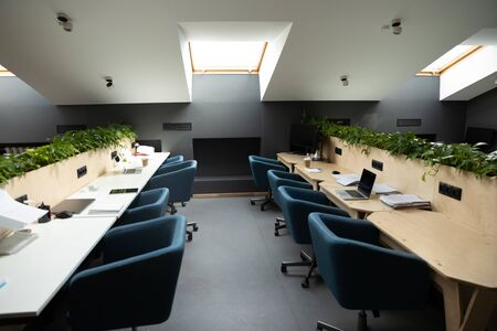 Empty workplace ideal conditions atmosphere for high productivity for freelancers or corporate team, room furnished with chairs shared table located in attic, concept of co-working modern open space