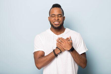 Glimlachende kalme Afro-Amerikaanse man in glazen geïsoleerd op blauwe studio achtergrond, hand in hand op hart borst biddend, dankbare biraciale mannelijke gelovige voelt zich gelukkig vreedzaam, dank God, geloof concept