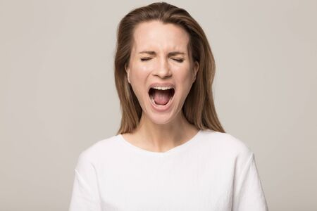 Angry millennial Caucasian woman in white t-shirt isolated on grey studio background scream yell, mad young female feel furious lose temper displeased stressed make loud noise, breakdown concept