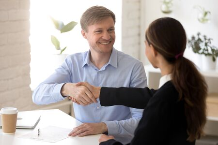 Head shot smiling confident male hr manager shaking hands with female job applicant, congratulating with successful employment. Happy man recruiter welcoming greeting woman work candidate at meeting. Фото со стока - 132348460