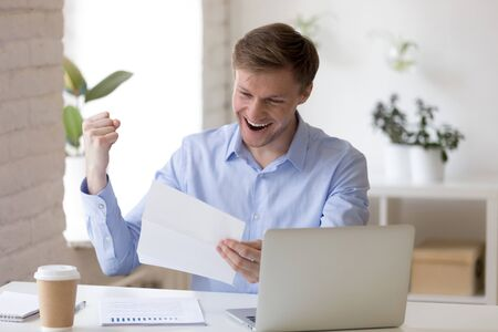 Euphoric middle aged businessman reading paper financial documentation, celebrating profitable deal or good project results. Happy young entrepreneur getting bank loan approval, feeling festive.