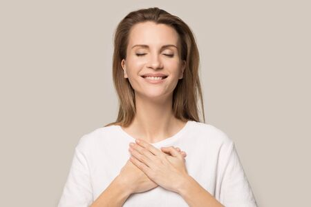 Happy Caucasian young woman in white tshirt isolated on grey studio background hold hands on heart chest feel thankful, smiling grateful millennial female thanking god, show love, empathy and care Stock Photo