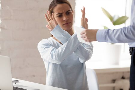 Angry millennial mixed race woman rejecting taking bribe for dark business schemes at workplace. Outraged female employee making refusing gesture, reacting to corruption deals at company office. 版權商用圖片