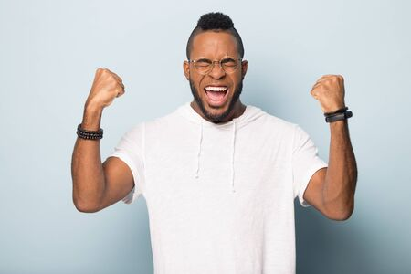 Overjoyed african American millennial man in glasses isolated on blue studio background feel euphoric celebrate victory success, excited happy biracial male winner triumph win lottery, reward concept