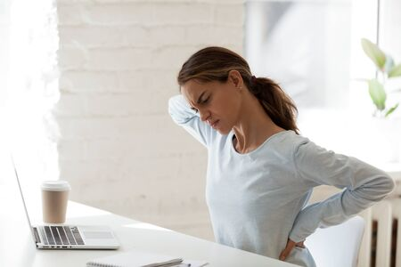 Side view fatigued young mixed race woman suffering from painful feelings in back due to long sedentary computer work at office or home. Unhealthy millennial female student having spine ache.