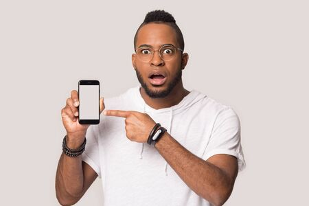 Close up shocked african American man in glasses isolated on grey studio background hold show cellphone screen stunned by news, amazed biracial male feel surprised demonstrate smartphone message Banque d'images - 132261977