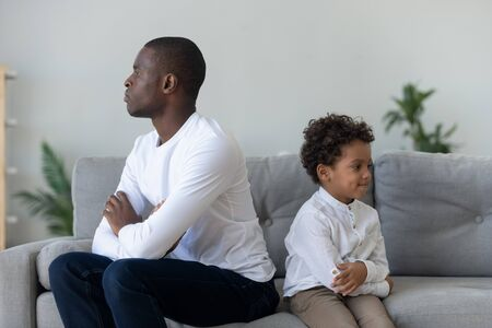 African American young dad and little biracial boy kid sit on couch back to back avoid talking after fight, stubborn ethnic father and small preschooler son ignore looking or speaking after conflict Stock Photo