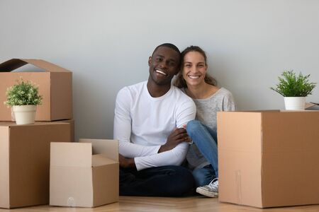 Portrait of smiling millennial international couple sit on floor surrounded by cardboard boxes move together to new home, happy multiracial family first time buyers look at camera excited to relocate