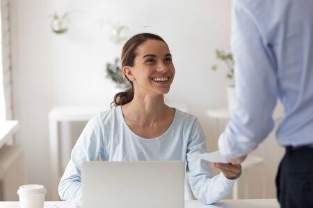 Kopfschuss junge, glückliche gemischte Rasse weibliche Mitarbeiterin, die Umschlag mit Geldbelohnung vom männlichen Chefteamleiter nimmt. Lächelnder biracial Manager zufrieden mit Bargeldbonus für großartige Arbeitsleistung im Büro.