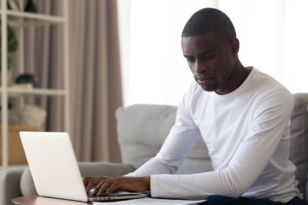 Focused african American man sit on couch busy with papers typing on laptop, concentrated biracial male employee or freelancer working from home, consider paperwork document using computer