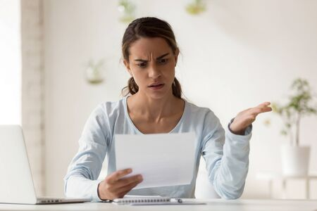 Head shot portrait stressed millennial mixed race woman reading paper with bad news. Frowning female employee irritated by dismissal notice. Unhappy young lady disagree with false information.