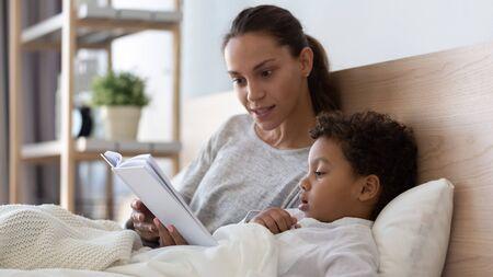Amante de la joven madre acostada en la cama con el pequeño hijo birracial leyendo un libro interesante, la madre solícita o la niñera ponen a dormir al pequeño niño en edad preescolar, relajándose en el dormitorio en casa juntos disfrutan de un cuento de hadas