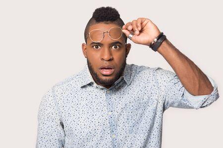 Ritratto di colpo alla testa di un uomo afroamericano scioccato che toglie gli occhiali guarda la telecamera stordito con un affare o un'offerta, stupito maschio birazziale isolato su sfondo grigio studio sentirsi sorpreso da notizie inaspettate