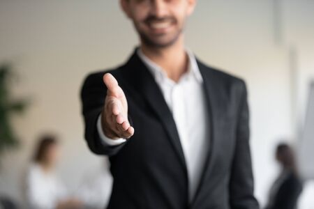 Professional business man hr consultant salesman wear suit extending hand at camera for handshake greeting offering cooperation, welcoming for collaboration, introduction concept, close up view