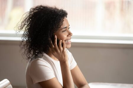 Side view head shot smiling happy african american young woman sitting at desk, talking on mobile phone with pleasant friend or husband, listening to good news, making taxi or food delivery order.