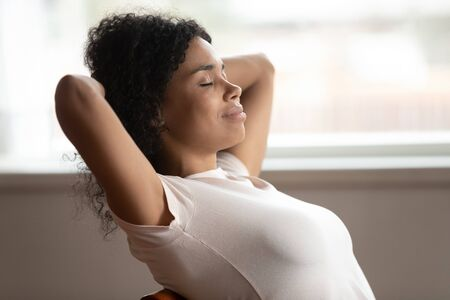 Peaceful african ethnicity young woman sitting on chair with crossed hands behind head, stretching back headshot. Happy black female freelancer relaxing, reducing stress, enjoying lazy day at home. 免版税图像