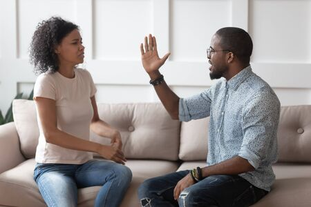 Mad african American young couple sit on couch arguing having family conflict, aggressive furious black husband raise hand intended to hit hurt millennial biracial woman suffer from domestic violence