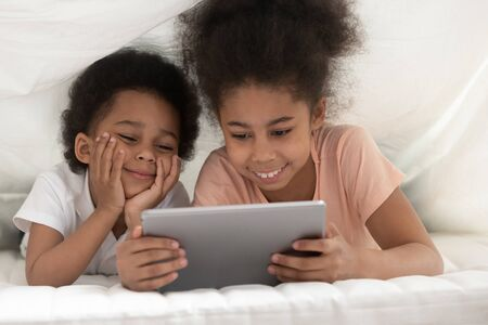 Smiling cute african American small sister and brother lying under white blanket watching funny cartoon on tablet together, happy boy and girl children have fun relaxing on bed under cover using pad