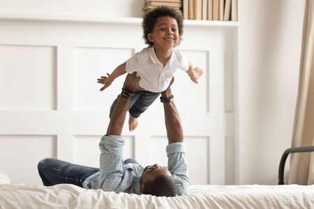 Loving african American dad lying on bed playing with cute little toddler son acting plane, happy black father have fun engaged in funny activity with small kid hold lift in arms in bedroom Stockfoto