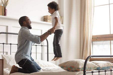 Happy loving african American young dad enjoy playing with toddler son have fun together in bedroom, smiling caring black father hold lift laughing small boy child jumping on bed spend weekend at home Stockfoto