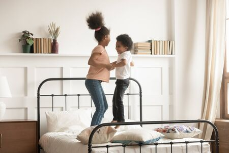 Overjoyed playful african American small brother and sister laugh playing jumping on bed at home, excited happy black boy and girl kids feel energetic have fun engaged in funny activity in bedroom