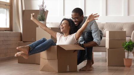 Overjoyed african American couple have fun feel euphoric moving together to new apartment, happy black husband ride smiling playful wife in cardboard box excited for relocation to own house