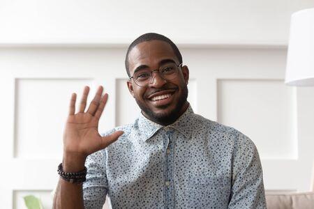 Lächelnder afroamerikanischer Tausendjähriger Mann mit Brille schaut auf die Kamera, die winkt und sagt Hallo beim Videoanruf, glücklicher schwarzer männlicher Vlogger in Brillengruß mit Abonnenten, die Videoblog schießen Standard-Bild