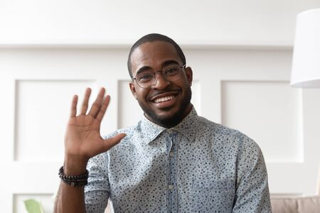 Smiling african American millennial man in glasses look at camera waving saying hello talking on video call, happy black male vlogger in spectacles greeting with subscribers shooting video blog Stock Photo