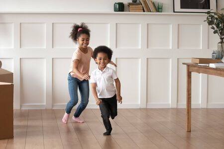 Excited smiling preschooler kids run in new empty home feel happy to move, overjoyed small brother and sister laugh have fun chasing each other playing in living room together. Entertainment concept