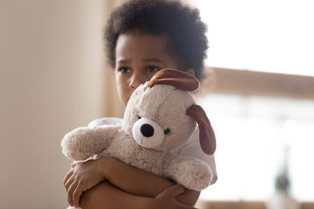 Unhappy mixed race little boy stand hugging stuffed teddy bear feel lonely lacking attention or communication, hurt small biracial kid hold plush toy suffer from loneliness, need parents Stock Photo