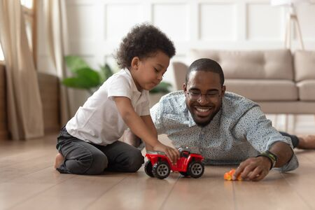 Smiling loving african American dad lying on floor playing with toddler son with toy cars at home, happy caring black father have fun with little kid engaged in funny activity race on automobiles Banco de Imagens