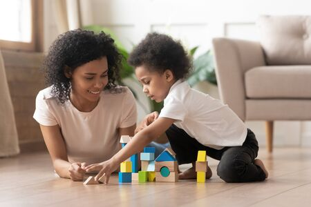 Caring african American smiling mom or nanny lying on floor playing with little boy kid with toy blocks, happy loving black mother enjoy funny learning activity with toddler son with building bricks