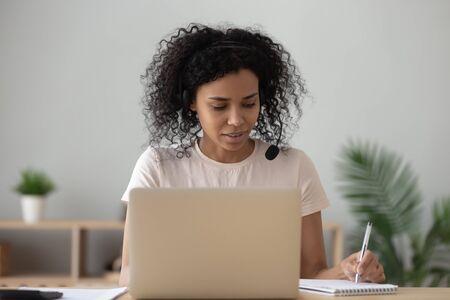 Konzentrierte afroamerikanische Studentin im Headset sitzt am Schreibtisch und macht Notizen mit dem Laptop