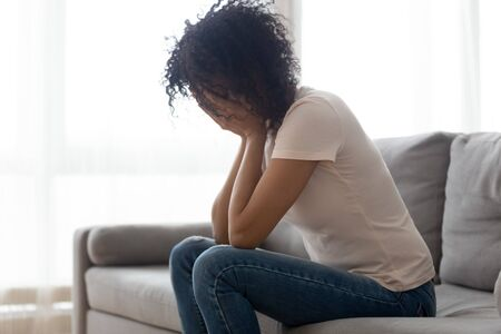 Desperate african American young woman sit on couch at home crying suffering miscarriage or abortion, depressed black female feel upset stressed having relationships split or breakup problems