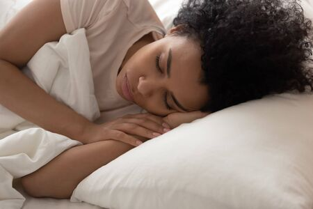 Close up of tired african American young woman lying in comfortable white bed relax seeing dreams, peaceful biracial black girl rest in bedroom sleeping on cozy fluffy non allergenic pillow