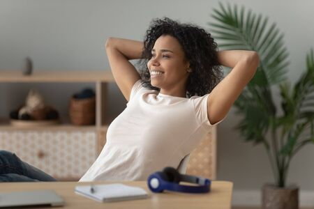 Happy calm african American millennial girl sit lean back in chair hands over head look in distance dreaming visualizing, smiling black young woman relax at workplace take pause distracted from work 写真素材