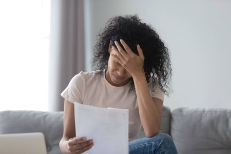 Stressed african American young woman hold paper document feel distressed with eviction notice or dismissal notification, upset black female read letter get bad news from correspondence mail