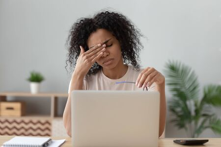 Unhealthy african American young woman sit at desk distracted from work take off glasses having migraine or headache, sick black millennial female rub eyes suffer from astigmatism sight problems