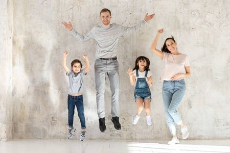 Full length overjoyed young parents with little cute kids siblings jumping, playing active game. Happy family married couple with two small children having fun together, enjoying weekend leisure time. Zdjęcie Seryjne