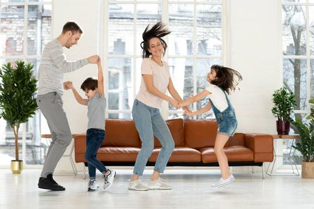 Overjoyed active parents dancing to favorite music with happy kids at living room at home. Happy dad and mom holding hands of adorable school children, twisting, having fun, celebrating occasion.