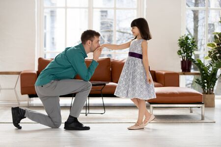 Full length young father standing on knee, kissing hand of smiling little daughter, looking at eyes, inviting for dance. Joyful small school girl ready training performance on modern living room.