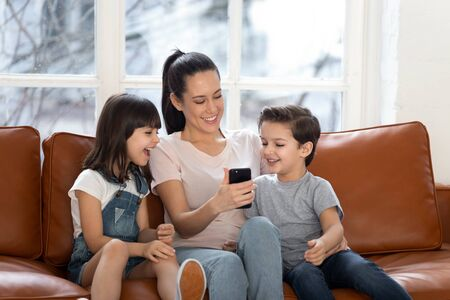 Happy young mommy sitting with children siblings, holding mobile phone in hands, showing funny video to kids, laughing, having fun together, using shopping application in living room at home.