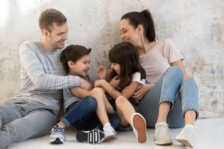 Happy young parents with little daughter and son sitting together on warm heated wooden floor at home. Smiling mother and father cuddling two playful tickling children siblings, enjoying free time.