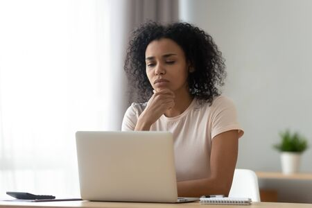 Pensive african American young woman sit at desk thinking studying or working on laptop at home, thoughtful black millennial girl student pondering considering idea looking at computer screen Banco de Imagens