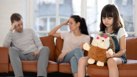 Little upset unhappy girl sitting on couch at home separately from arguing parents, feeling depressed frustrated, suffering from mommys and daddys conflict, misunderstanding. Family problem concept. Stock Photo