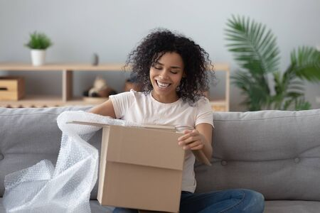 Smiling african American millennial girl sit on sofa at home open cardboard delivery package shopping online, excited black young woman unpack unwrap parcel buying good via internet or web Zdjęcie Seryjne