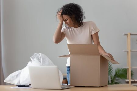 Disappointed african American millennial girl unpacking cardboard delivery box frustrated by delivered product, upset confused black young woman shopping online unwrap open bad quality product