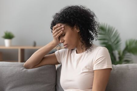Depressed black young woman sit on sofa down upset having personal relationships problems, stressed millennial african American girl touch head feel despair mourning or grieving of loss Stock Photo