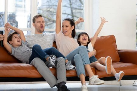 Overjoyed family of four, dad mom and children sport fans sitting on couch in living room at home watching football basketball match on tv with favorite team, celebrating goal or championship win. Zdjęcie Seryjne