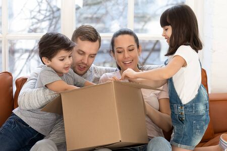 Curious happy parents holding big carton box, unpacking delivery parcel with joyful little daughter and son. Cheerful family buyers received order from popular online internet store, looking inside.